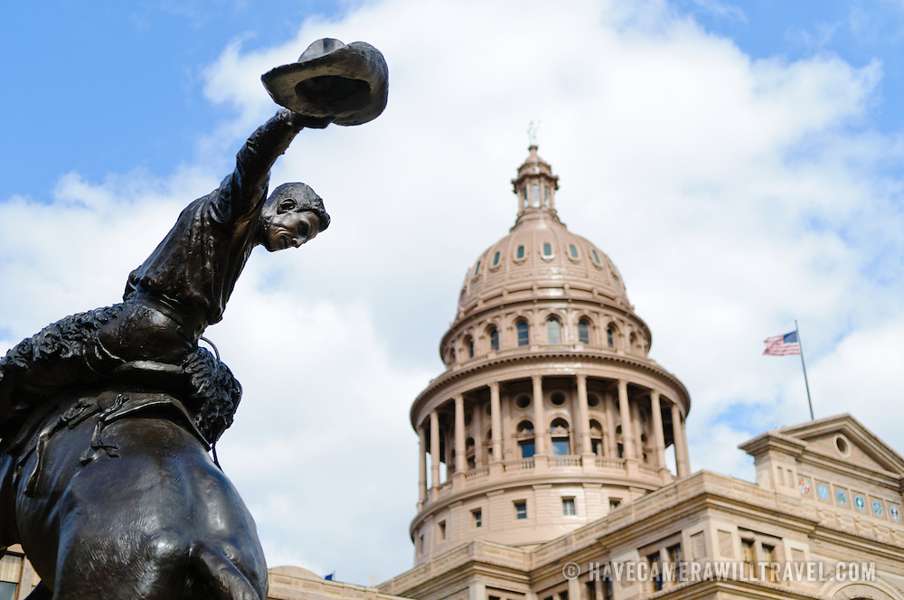 In the foreground is a bronze statue of a cowboy on a horse in the grounds of the Texas State Capitol in Austin. The artist was Constance Whitney Warren and it was unveiled on January 17, 1925. The building is built in the style of Italian Renaissance Revival.