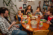 Michael Sturm family at suppertime in Hamburg, Germany. At supper Astrid Hollmann, 38, and Michael Strum, 38, and their three children Lenard, 12, Malte Erik, 10, and Lillith, 2.5They were photographed for the Hungry Planet: What I Eat project with a week's worth of food. Model Released.