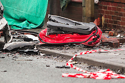 © Licensed to London News Pictures . 08/02/2013 . Salford , UK . Pictured the remains of a red Audi on its side with its door lying on the pavement . The scene on Leigh Road where a multi-vehicle pile up killed two , sparked a fire and damaged several cars and houses overnight , causing residents to be evacuated . Greater Manchester Police report seeing a stolen red Audi which they attempted to pursue prior to the crash . Photo credit : Joel Goodman/LNP
