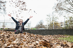 Young man throwing autumn dry leaves in air, Munich, Bavaria, Germany