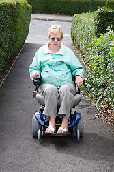 Woman wheelchair user travelling down an alleyway,
