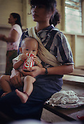 DAYAK COCA COLA, MALAYSIA. Sarawak, Borneo, South East Asia. Dayak baby drinking Coca Cola fizzy drink from can, during church  service. Tropical rainforest and one of the world's richest, oldest eco-systems, flora and fauna, under threat from development, logging and deforestation. Home to indigenous Dayak native tribal peoples, farming by slash and burn cultivation, fishing and hunting wild boar. Home to the Penan, traditional nomadic hunter-gatherers, of whom only one thousand survive, eating roots, and hunting wild animals with blowpipes. Animists, Christians, they still practice traditional medicine from herbs and plants. Native people have mounted protests and blockades against logging concessions, many have been arrested and imprisoned.