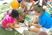 Girls age 6 blow painting with girl 4-H leader age 15 at Minnesota State Fair.  St Paul Minnesota USA
