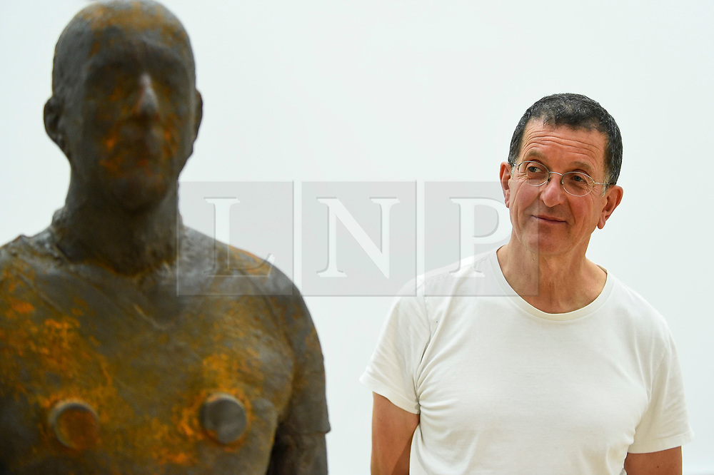 """© Licensed to London News Pictures. 16/09/2019. LONDON, UK.  Antony Gormley RA poses next to his work """"Lost Horizon I"""", 2008, which comprises 24 cast iron body forms.  Preview of a new exhibition by Antony Gormley at the Royal Academy of Arts.  The show bring together existing and specially conceived new works from drawing to sculptures to experimental environments to be displayed in all 13 rooms of the RA's Main Galleries 21 September to 3 December 2019.  Photo credit: Stephen Chung/LNP"""