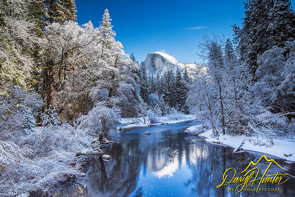 Yosemite under a blanket of new snow with Half Dome towering above and reflecting in the Merced River Below.