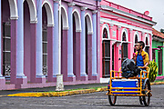 A vendor rides his cargo cycle past colorful colonnade style buildings in Tlacotalpan, Veracruz, Mexico. The tiny town is painted a riot of colors and features well preserved colonial Caribbean architectural style dating from the mid-16th-century.