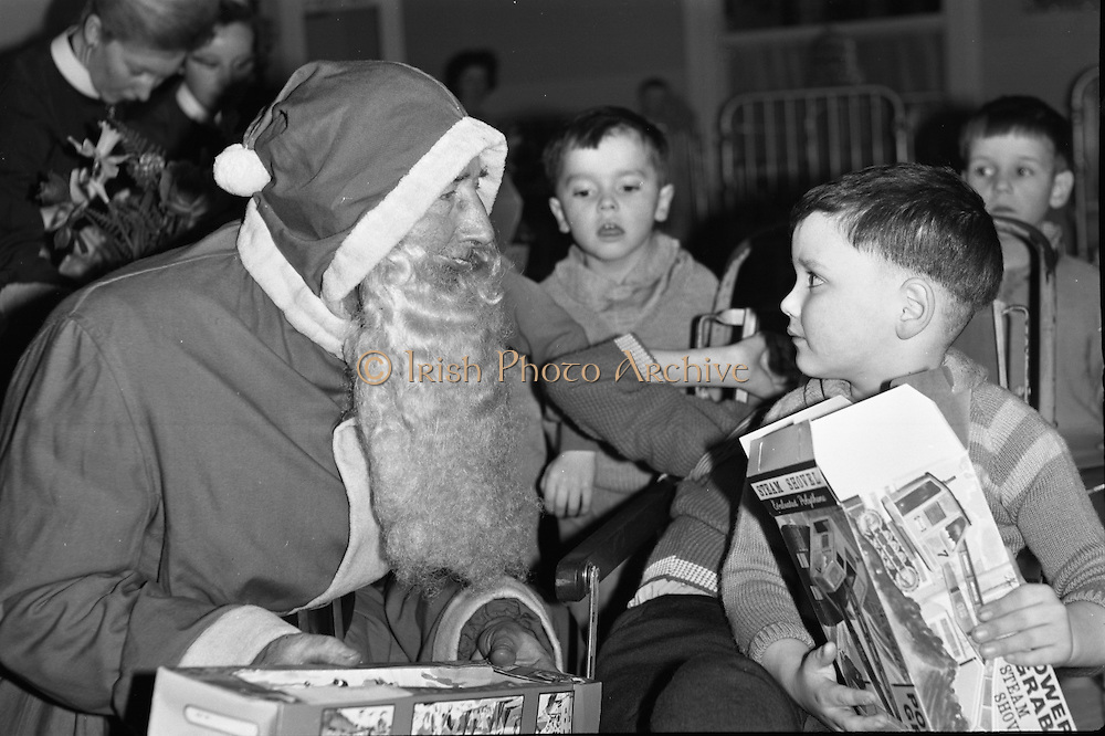 Prescott's Party for Children at St. Mary's Hospital, Baldoyle..1964..16.12.1964..12.16.1964..16th December 1964..At St Mary's Hospital in Baldoyle,Dublin, Prescotts Cleaners and Dyers sponsored a party for the disabled children who are resident there...Image shows Santa having a quiet word with this young man discussing what he would like for Christmas.