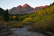 Fall comes to the Maroon Bells, with Maroon creek running peacefully in the foreground.
