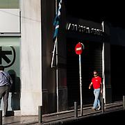 People passing by Alpha bank  in Mitropoleos Str,  Athens, Greece