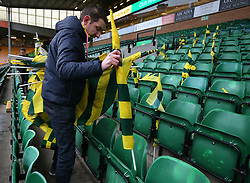 Norwich City staff place flags on seats before the game against Ipswich Town during the Premier League match at Carrow Road, Norwich.