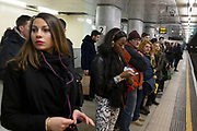 People waiting on the platform at Embankment underground station, London, UK. This public transport tube station is on the District and Circle lines from this platform.