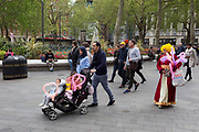 A foreign family walk with their children in a buggy and who have just purchased heart-shaped balloons in Leicester Square, on 29th April 2019, in London, England.