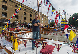 © Licensed to London News Pictures.  03/09/2021. London, UK. Ian Gilbert the owner of the Lady Lou poses for a photo at St Katharine Docks Marina on the River Thames ahead of the Classic Boat Festival this weekend. With 40 vintage sail and motor yachts, the Classic Boat Festival is part of Totally Thames' 25th festival. Photo credit: Marcin Nowak/LNP