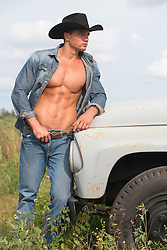 hot young cowboy with an open shirt standing near a vintage truck