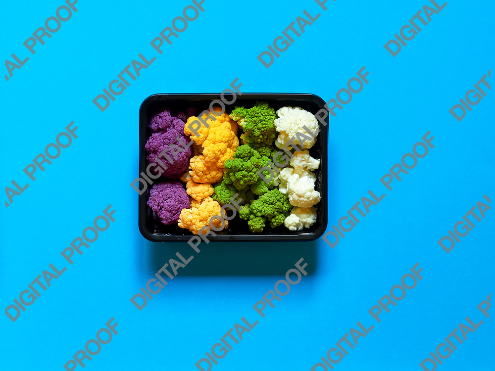 Set of seasonal and colorful cauliflower violet, yellow, green and white boxed in a plastic recipient over a light blue background