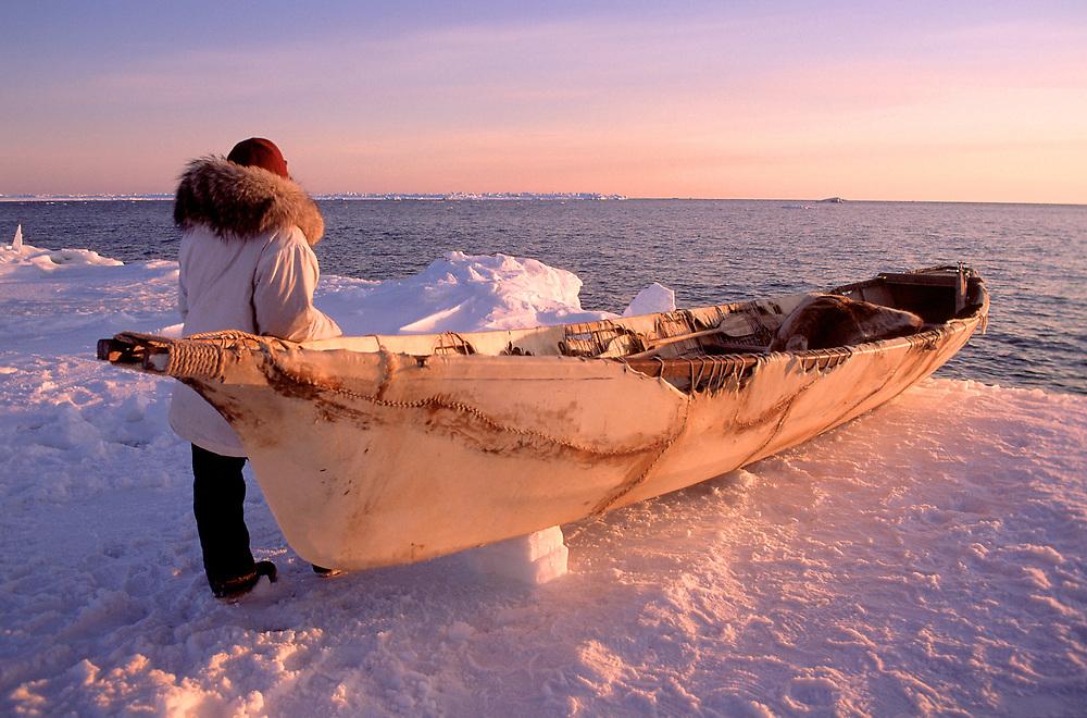 Sunset over a native whaler and the crew's umiak on the frozen sea ice near Barrow, Alaska