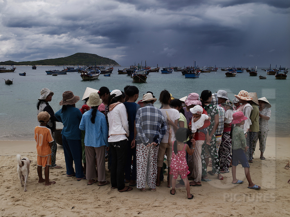 A group of vietnamese women gather on the beach and overlook at the fishermen's catch. Phan Thiet, Vietnam, Asia