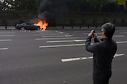 A passer-by films a Mercedes as it burns at the side of the road at Hyde Park Corner in central London.