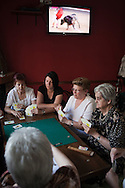 BERROCALEJO, SPAIN: A group of women play cards while the TV shows a bullfight at a bar in Berrocalejo, Cáceres, Spain.