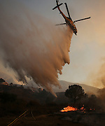 A helicopter makes a drop on a wildfire near Placenta Canyon Road in Santa Clarita, Calif., Sunday, July 24, 2016.(AP Photo/Ringo H.W. Chiu)
