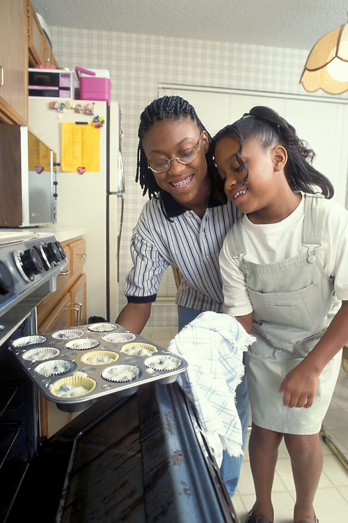 African-American sisters (ages 14 and 8) cooking blueberry muffins together at home in the kitchen.  Model Release.<br /> ©Bob Daemmrich