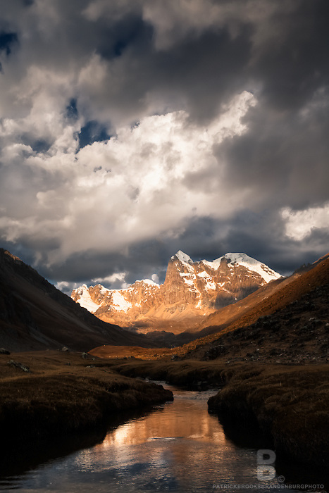 A stream and reflection of west facing slope of Mt Cuyoc as the sun light is golden in the Cordillera Huayhuash in the Andes Mountains of Peru.