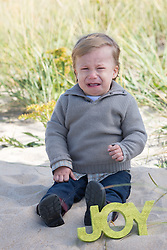 baby crying next to the word Joy at the beach