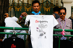 © Licensed to London News Pictures. 19/01/2014. An Anto-Government security guard holds up a ripped T-Shirt as a result of the grenade attack at a street side vendor .The grenade attack has reportedly injured 28 people at the protest site at the Victory Monument in Bangkok Thailand. Anti-government protesters launch 'Bangkok Shutdown', blocking major intersections in the heart of the capital, as part of their bid to oust the government of Prime Minister Yingluck Shinawatra ahead of elections scheduled to take place on February 2. Photo credit : Asanka Brendon Ratnayake/LNP