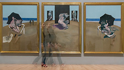 "© Licensed to London News Pictures. 26/02/2018. LONDON, UK. A multiple exposure of a staff member walking in front of ""Triptych"", 1974-1977, by Francis Bacon.  Preview of ""All Too Human"", an exhibition at Tate Britain which explores how artists in Britain have stretched the possibilities of paint in order to capture life around them.  The exhibition runs 28 February to 27 August 2018 and includes rarely seen works by Lucian Freud and Francis Bacon.  Photo credit: Stephen Chung/LNP"
