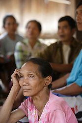 People gather for an Older People's Group meeting where they will discuss individual and group needs.  Chang Nga 55 years old smiling at some of the comments.<br /> Had Yen Village, Pakseng District, Luang Prabang Province, Lao PDR