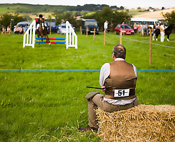 © Licensed to London News Pictures.12/08/15<br /> Danby, UK. <br /> <br /> A man sits and watches a show jumping event during the 155th Danby Agricultural Show in the Esk Valley in North Yorkshire. <br /> <br /> The popular agricultural show attracts competitors and visitors from all over the surrounding area to this annual showcase of country life. <br /> <br /> Photo credit : Ian Forsyth/LNP