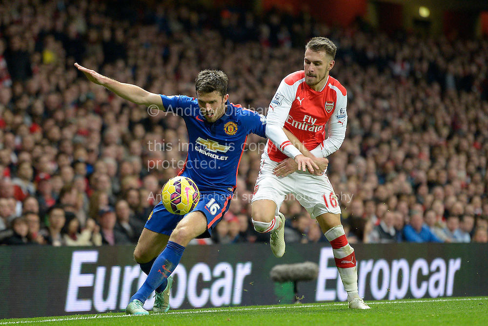 Michael Carrick of Manchester United holding the ball from Aaron Ramsey of Arsenal. Barclays Premier league match, Arsenal v Manchester Utd at the Emirates Stadium in London on Saturday 22nd November 2014.<br /> pic by John Patrick Fletcher, Andrew Orchard sports photography.