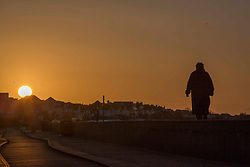 © Licensed to London News Pictures.27/03/2021. Southend-On-Sea,UK. A woman walks by the beach in Southend-On-Sea, Essex during the sunrise. Weather forecasts predict sunny weather with strong winds in the south-east of England.   Photo credit: Marcin Nowak/LNP