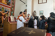 Istanbul, Turkey. Men and women in the congregation of the Samatya Kilisesi line up to take communion offered by the Syriac bishop in the diverse church in Istanbul's historic Fatih neighbourhood. The bible pictured is in Syriac, a dialect of Aramaic.