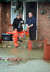 © London News Pictures. 12/02/2014. Egham, UK.  Residents poor flood water from their wellington boots on their doorstep in Egham, Surrey, which has been hit by heavy flooding. Torrential  rain in the area is due to raise water levels increasing the risk of further flooding. Photo credit : Ben Cawthra/LNP
