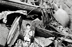 Photograph of schoolboy lies amongst debris of a demolished house in a Beijing hutong