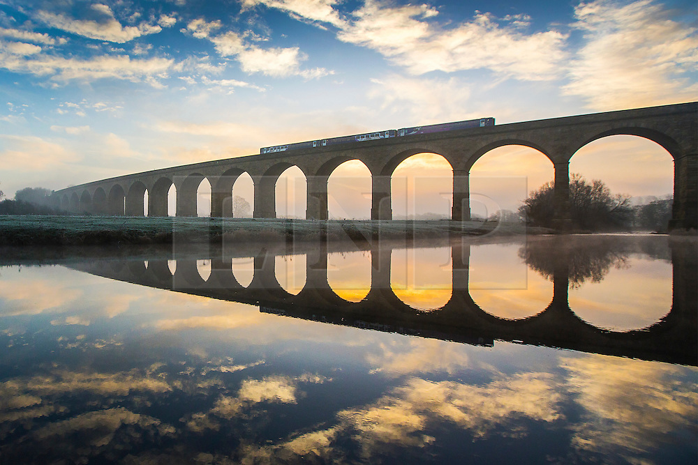 © Licensed to London News Pictures. 24/01/2017. Arthington UK. A commuter train crosses Arthington Viaduct in Yorkshire at first light this morning as the country woke to more fog & ice. Photo credit: Andrew McCaren/LNP