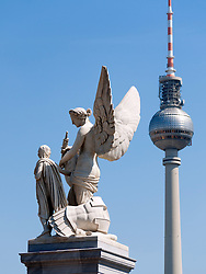 Detail of ornate statue on bridge on Unter den Linden and TV Tower or Fernsehturm in Mitte Berlin  Germany