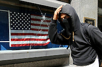 A demonstrator passes by a crack window smashed during a protest march from the Minnesota State Capitol to the Xcel Energy Center in St. Paul, Minnesota, before the start of the Republican National Convention, Monday, September 1, 2008.