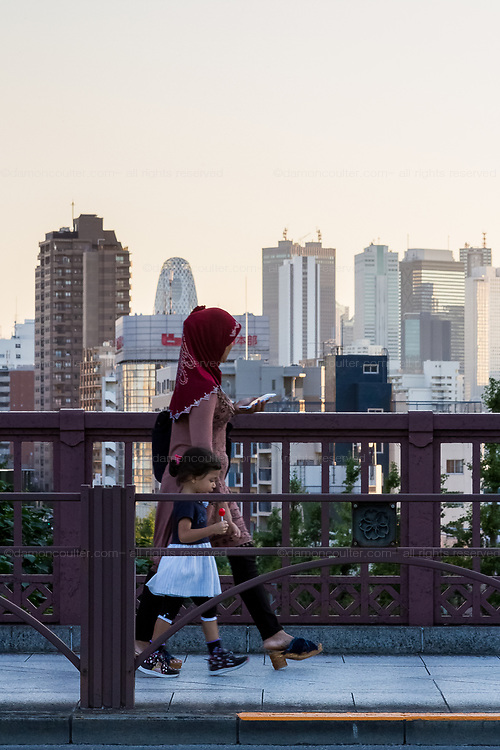 A Muslim Immigrant  mother and her child walk on the street in Zoshigaya with the skyscrapers of Shinjuku behind. Tokyo, Japan. Friday September 28th 2018 Immigration levels in Japan remain low with over 98% of the population remaining ethnically Japanese. Nearly 70,000 people immigrated to the country in 2017 and this despite reluctance from many Japanese is likely to increase as the native population ages and declines.