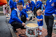 A toddler tries his skills and playing the drum. Orange March, Belfast, NI, 2021