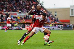 Swindon Defender Louis Thompson (ENG) is challenged by Bristol City Midfielder Marvin Elliott (JAM) during the second half of the match - Photo mandatory by-line: Rogan Thomson/JMP - Tel: 07966 386802 - 21/09/2013 - SPORT - FOOTBALL - County Ground, Swindon - Swindon Town v Bristol City - Sky Bet League 1.