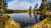 Sky and trees reflect in Sylvan Lake, Yellowstone National Park, Wyoming, USA. Yellowstone was established as the world's first national park in 1872 and was listed by UNESCO as a World Heritage site in 1978. This image was stitched from multiple overlapping photos.