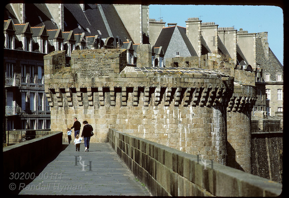 Mother and father lead two daughters along battlements of the fortress city of Saint Malo. France