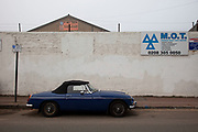 Old MGB Midget car parked outside an MOT centre in Deptford, London. The Ministry of Transport test (usually abbreviated to MOT test) is an annual test of automobile safety, roadworthiness aspects and exhaust emissions required for most vehicles over three years old used on public roads in the United Kingdom.