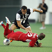 Newcastle United Defender Sanchez Jose Enrique (3) trips up Forward Matt Luzunaris (12) during an International Friendly soccer match between English Premier League team Newcastle United and the Orlando City Lions of the United Soccer League, at the Florida Citrus Bowl on Saturday, July 23, 2011 in Orlando, Florida. Orlando won the match 1-0. (AP Photo/Alex Menendez)