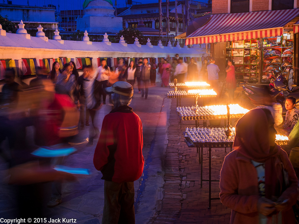 31 JULY 2015 - KATHMANDU, NEPAL:  The full moon procession at Bodhnath Stupa. Bodhnath Stupa in the Bouda section of Kathmandu is one of the most revered and oldest Buddhist stupas in Nepal. The area has emerged as the center of the Tibetan refugee community in Kathmandu. On full moon nights thousands of Nepali and Tibetan Buddhists come to the stupa and participate in processions around the stupa. The stupa was heavily damaged in the earthquake of 25 April 2015 and people are no longer allowed to climb on the stupa, now they walk around the base and pray with butter lamps.  PHOTO BY JACK KURTZ