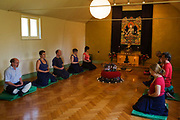 Buddhists meditate in silence for 30 minutes in their Shrine Room at the Rivendell Buddhist Retreat Centre, England. A middle-aged man and a younger woman sit in a meditative cross-legged position in order to relax their bodies and free their minds for this period of inner-contemplation. In the middle on a polished parkay floor is a model of their retreat centre, a house now run by the Triratna Buddhist Community. Once a Victorian country rectory for the local vicar in this East Sussex village, it now houses facilities for the spiritual and the peaceful, having escaped for a brief time, the pressures of modern life. Beyond are two Buddhas on a tapestry and as a statue. The community web address is www.rivendellretreatcentre.com.