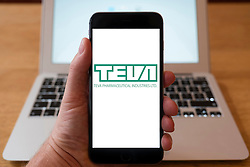 Using iPhone smartphone to display logo of Teva Pharmaceutical Industries Ltd; Israeli multinational pharmaceutical company