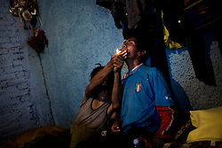 One man helps another smoke crack in Mexico City.  Drugs use has been rising in Mexico City.  Low level dealers are now paid more often in drugs instead of money, and increased border security causes more drugs to stay in the country.  In the capital many homeless children and adults are addicted to sniffing paint thinner and also to crack.